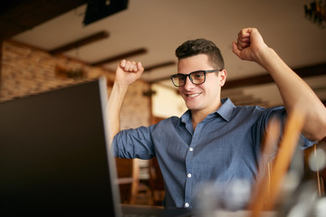 Handsome businessman with laptop having his arms with fists raised, celebrating success. Happy freelancer hipster in glasses finished work on project. Man won a lot of money in lottery prize.