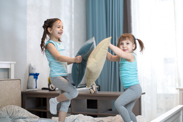 kids girls have fun playing with pillows at home