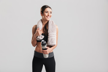 Healthy beautiful sportswoman wearing tracksuit with towel looking aside and holding bottle with fresh water, isolated over gray background
