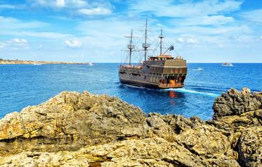 The bridge of love or love bridge. Pirate ship sailing near famous Bridge of Love near Ayia Napa, Cyprus.