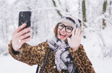 Attractive girl wears glasses have videochat by smartphone in winter snowy park
