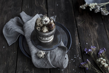 Quail eggs in metal rustic bowl on wooden country table on linen napkin