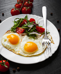 Breakfast. Fresh salad and two fried eggs on dark wooden background