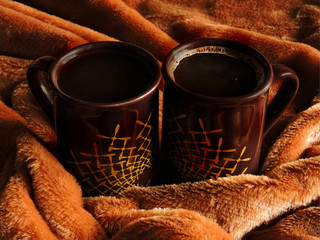 Two cups of fragrant coffee in a soft plaid of coffee color