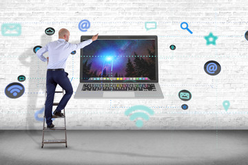 Businessman in front of a wall with a computer surrounding by app and social icon - 3d render