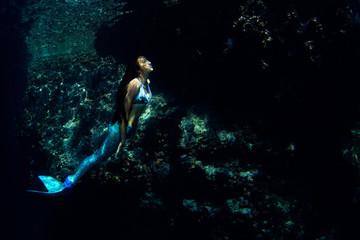 Mermaid swimming underwater in the deep blue ocean