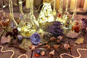 Witch magic collection with lightning bottles, crystals, pentagram, old key and herbs. Occult, esoteric, divination and wicca concept. Halloween background with vintage objects