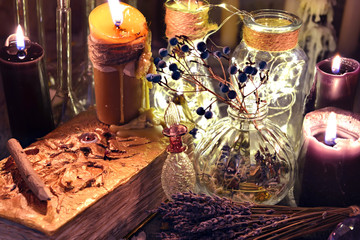 Evil book with black candles, glass bottles, and herbs on witch table. Occult, esoteric, divination and wicca concept. Halloween background with vintage objects