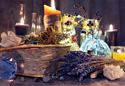 Old witch book with lavender flowers, crystal and evil candles. Occult, esoteric, divination and wicca concept. Halloween background with vintage objects