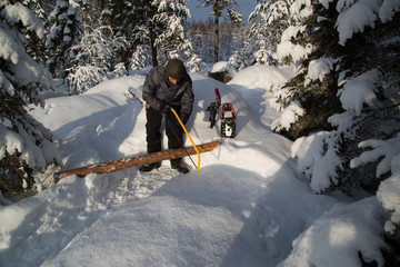 Campfire in deep snow, preparation, 5. step: sawing thick wood for a pad/base, protection against moisture and cold