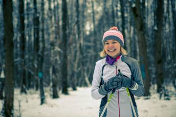 Image of smiling woman with skis in winter forest