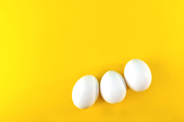 White chicken eggs on yellow background. Easter postcard.
