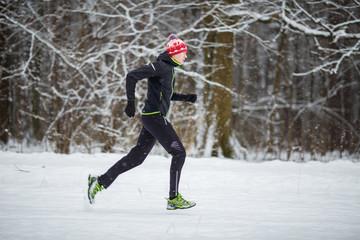 Image from side of man in sportswear, red cap on run in winter