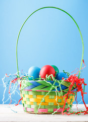 Photo of basket with colorful eggs on wooden table