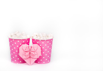 Two paper cups and valentine on white background. Cocoa, marshmallow and paper heart. Romantic concept. St. Valentine's Day. Copy space