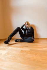 A beautiful young woman sitting on the floor and wearing black clothes.