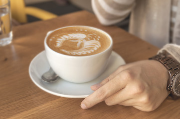 Girl holding espresso cup cappuccino in a cafe on a wooden table