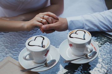 Wedding couple is sitting and holding arms. Nice cappuccino with foam and hearts on the table. Glass table and engagement golden ring.