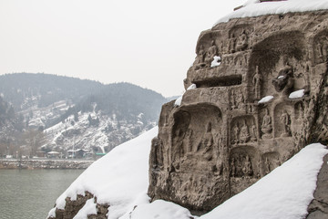 Stone Buddha Statue Carved from the mountains in the winter with snow