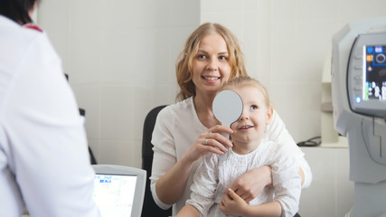 Optometrist in clinic checking little child's vision - medicine