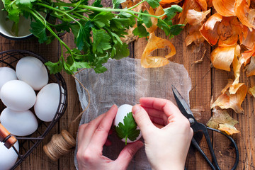 The process of dyeing eggs in onion peel with a pattern of parsley leaves, selective focus, top view