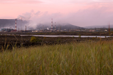Pollution of the environment by heavy industry. Industrial landscape at sunset sky. Metallurgical plant pollutes the air. Pipes with smoke on the horizon line.