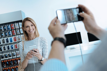 Pose on camera. Beautiful female person expressing positivity while testing new gadget and looking at her boyfriend