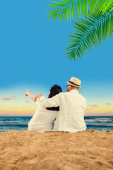 indian senior couple at beach - old indian man and wife relaxing on beach with fresh juice, pointing in sky, clicking selfie picture or taking a walk