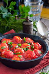 Meatballs in tomato sauce in a cast-iron frying pan, selective focus