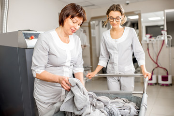 Senior washwoman and young assistant working in the hotel laundry