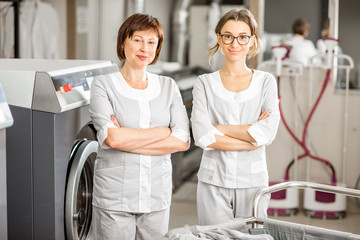 Portrait of a senior washwoman and young assistant standing together in the hotel laundry
