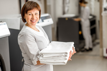 Portrait of a senior washwoman in uniform standing with bedclothes in the hotel laundry