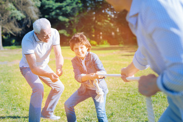 Cmon you can do it. Thoughtful senior man getting excited while encouraging his little grandson playing a tug of war game with his son.