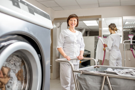 Senior washwoman in uniform standing with clothes basket near the wahing machine in the professional hotel laundry