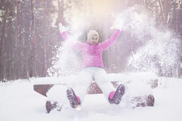 девушка в розовой куртке подбрасывает вверх снег сидя на скамейке в зимнем парке