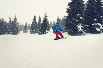 Snowboarder rides in a hard conditions during a blizzard