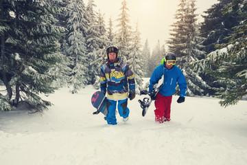Joyful snowboarders go up the mountain slope
