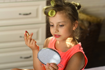 Child sits on bed with pink lipstick and looks in mirror