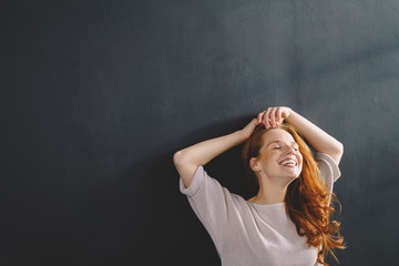 Laughing carefree young redhead woman
