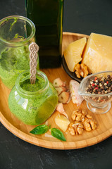 Basil walnut pesto in a jar with raw ingredients on a wooden plate. Black stone background.