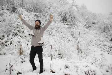 bearded happy man hold skate in snowy winter forest, christmas