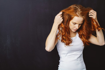 Young woman with long red hair looking down