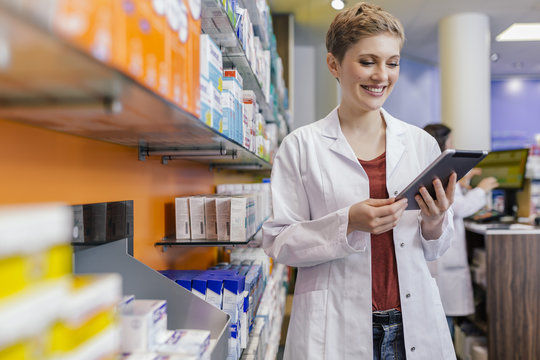 Smiling pharmacist at shelf with medicine in pharmacy holding tablet