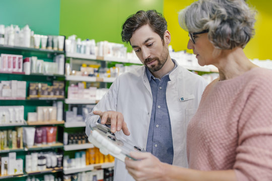 Pharmacist advising customer with scales in pharmacy
