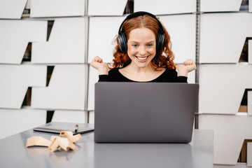 Happy business woman in headphones with laptop