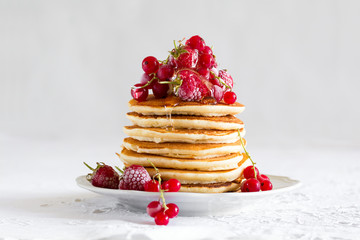 Stack of pancakes with raspberry, red currant, cream and honey on white table cloth