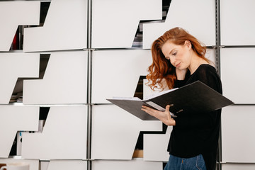 Businesswoman looking up information in a binder