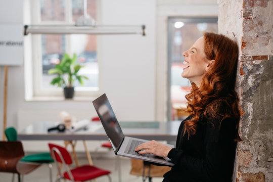 Young woman laughing at a good online joke