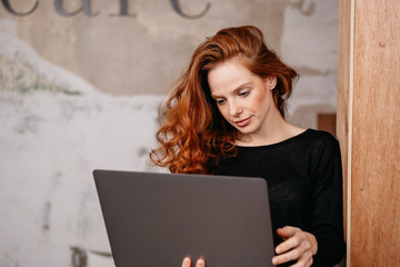 Attractive redhead woman looking at a laptop