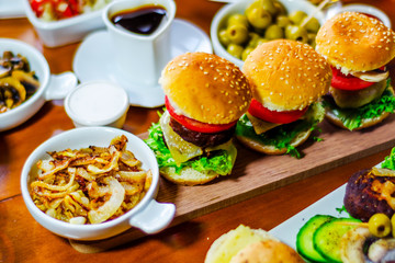 mini burgers with meat, vegetables, cheese and other toppings, bread sprinkled with sesame seeds, mini fast food